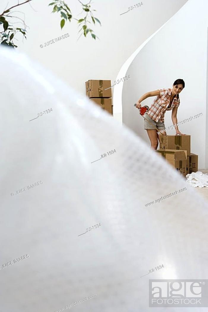 Stock Photo: Woman sealing box with tape at home, smiling, bubble wrap in foreground, focus on background.