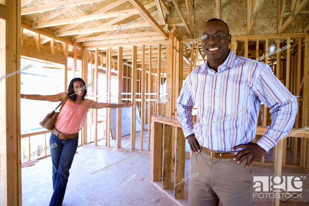 Stock Photo: Woman smiling at businessman with hands on hips in paritally built house, portrait.