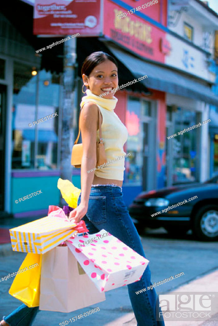 Stock Photo: Portrait of a young woman walking with shopping bags.