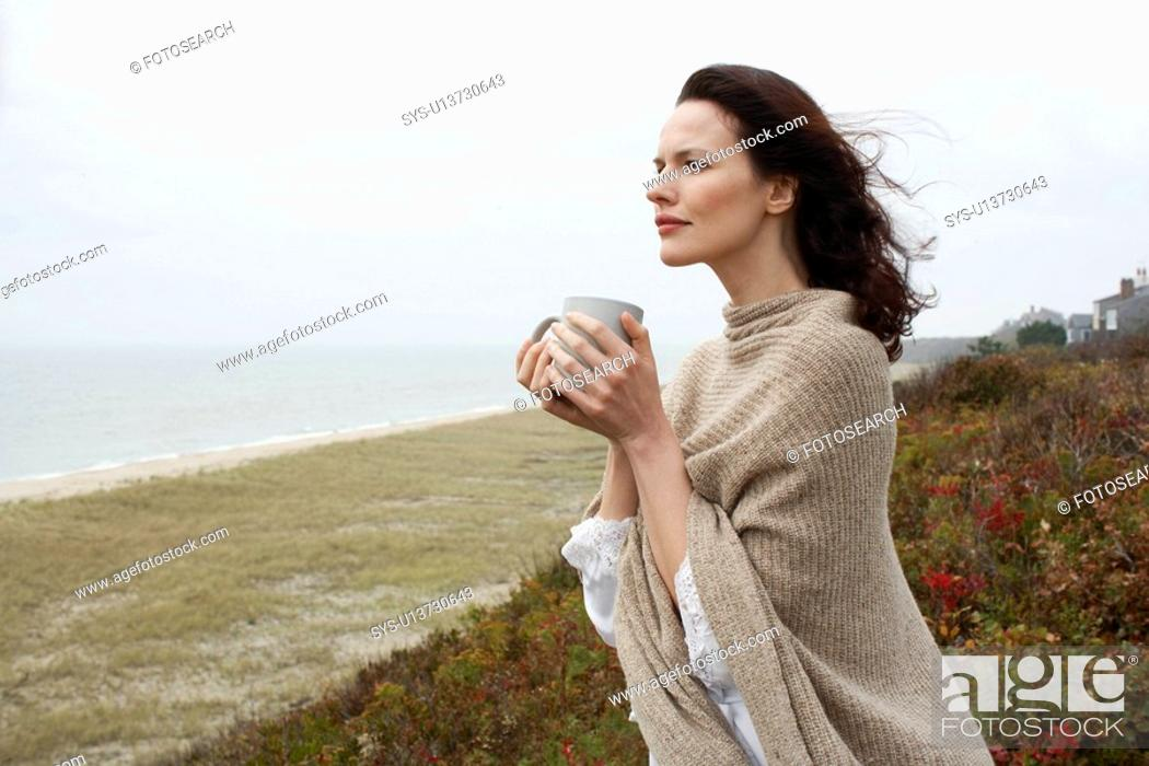 Stock Photo: Young woman drinking coffee at beach.