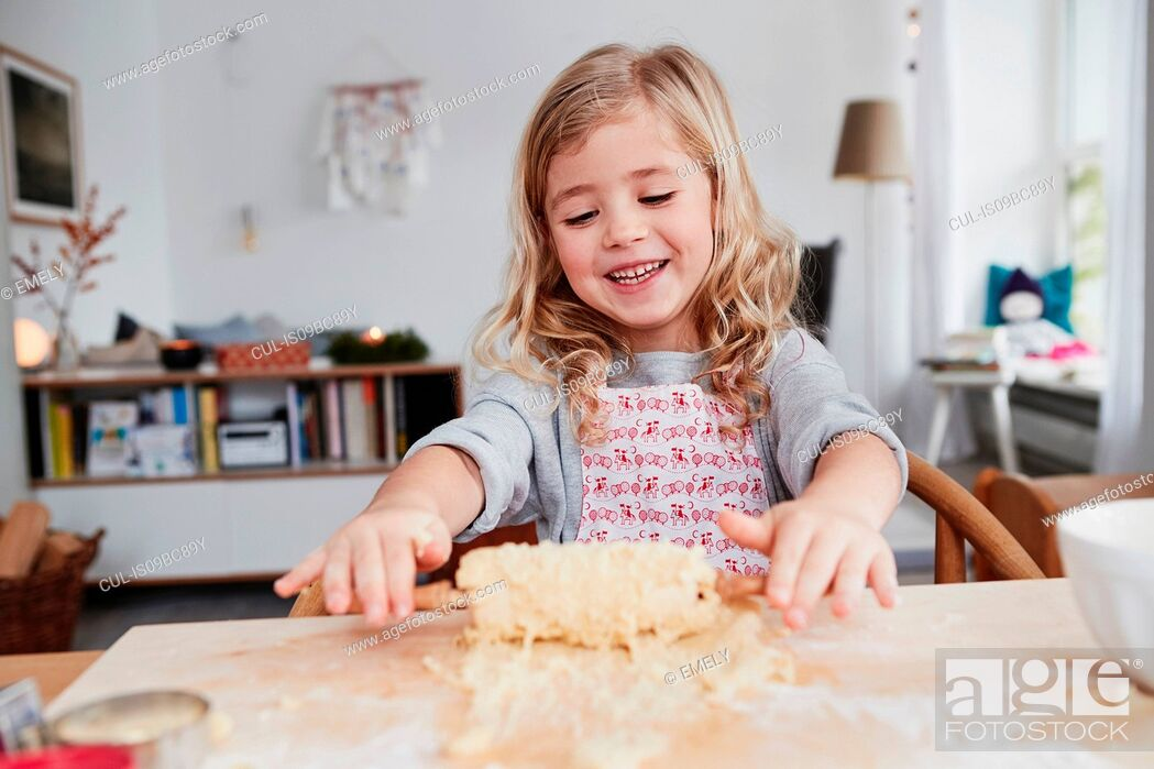 Stock Photo: Young girl rolling out cookie dough, dough stuck to rolling pin.
