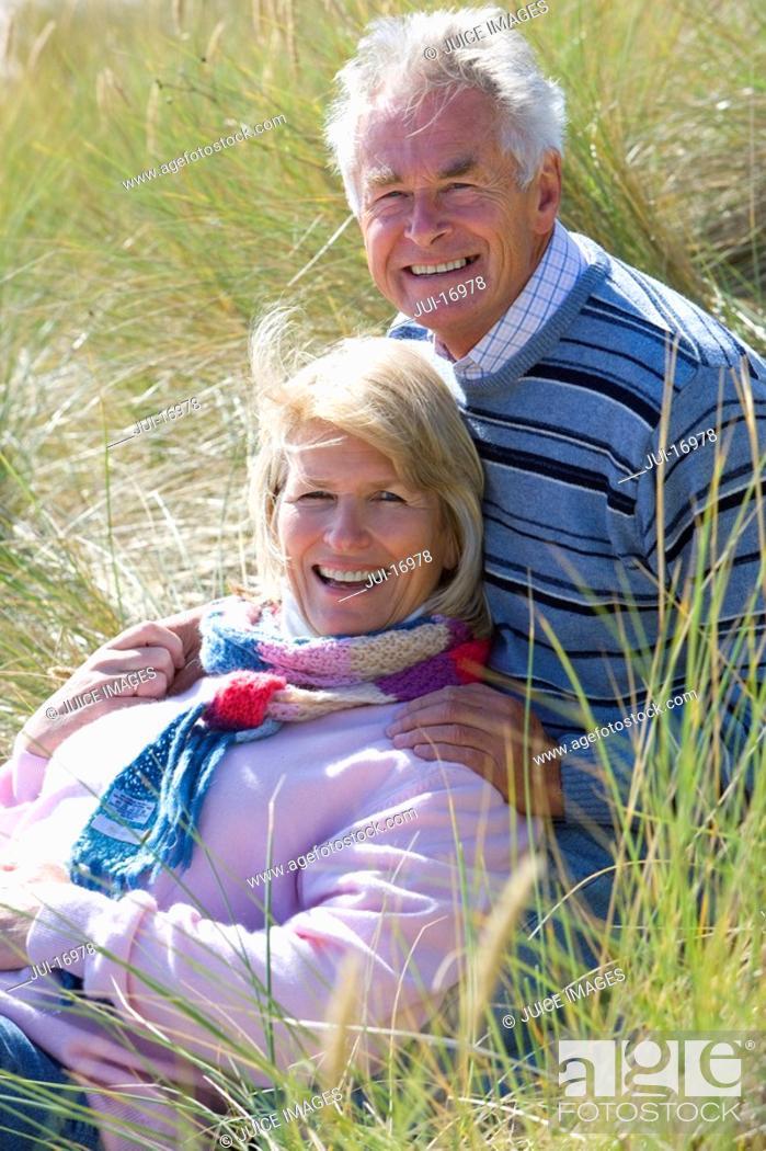 Stock Photo: Portrait of senior couple sitting on beach.