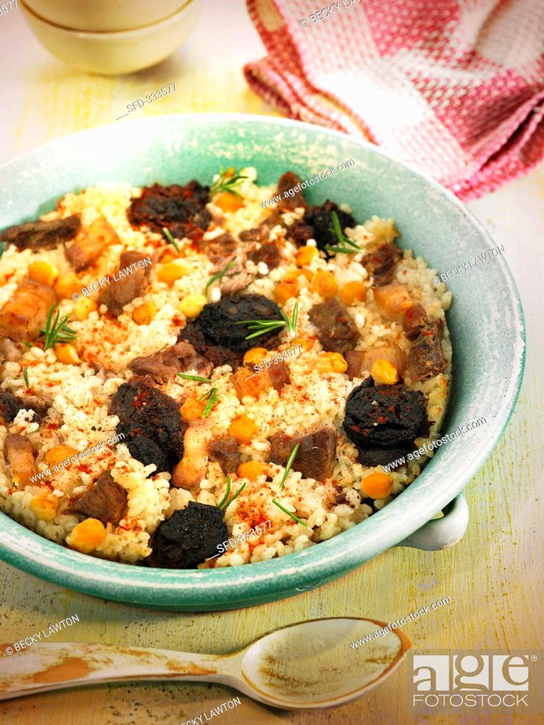 Stock Photo: Arroz al horno oven baked rice, Spain with morcilla, meat and chickpeas.