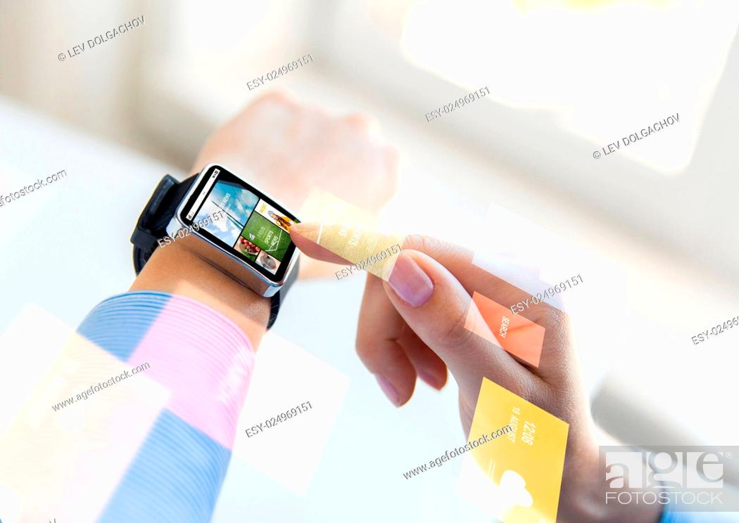 Stock Photo: business, modern technology, media, internet and people concept - close up of female hands setting smart watch with news web page on screen at office.