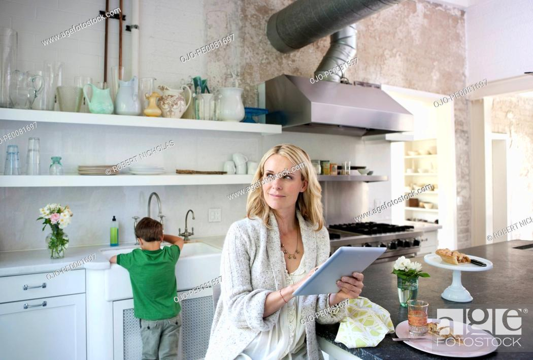Stock Photo: Mother using tablet computer in kitchen.