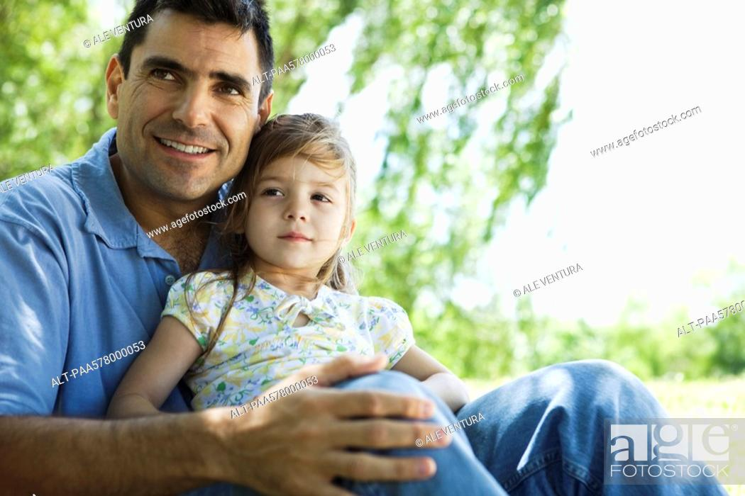 Stock Photo: Father holding young daughter on lap outdoors.
