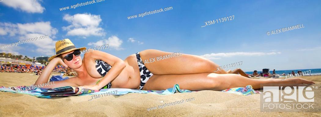 Stock Photo: Woman lying on the beach in a panoramic viewpoint.