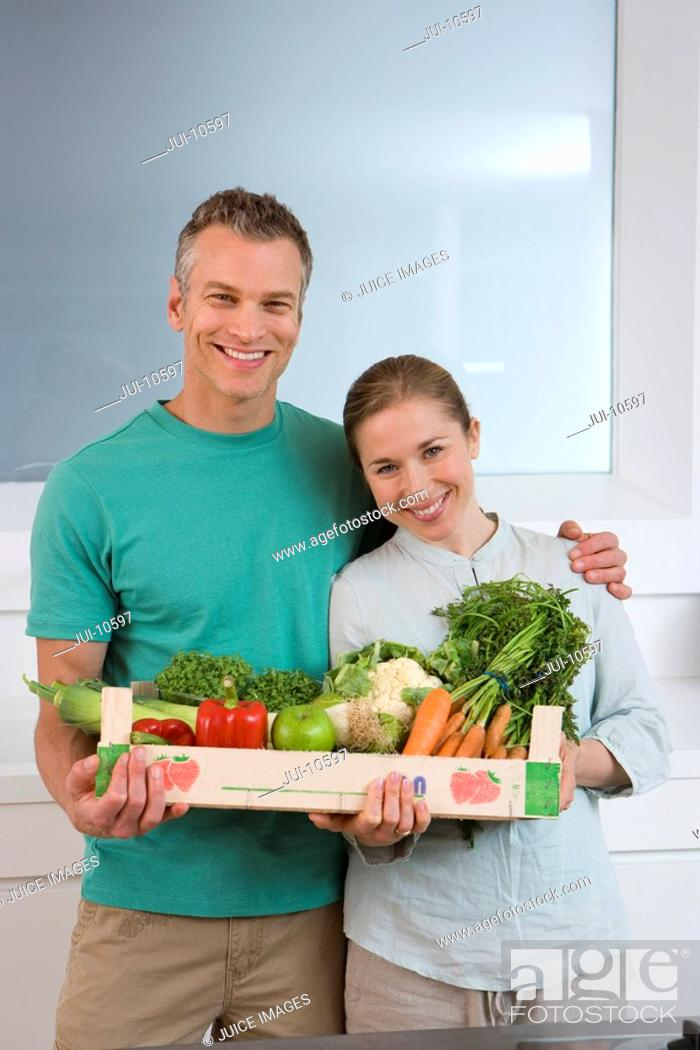 Imagen: Couple in kitchen with box of vegetables, smiling, portrait.