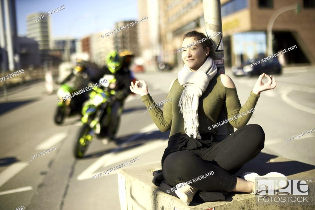 Photo de stock: relaxed woman meditating in middle of street next to traffic, in Hamburg, Germany.