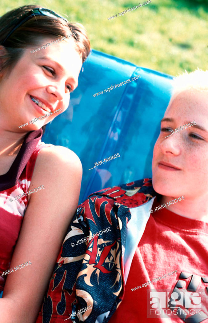 Stock Photo: A boy and a girl, a young couple or friends, are sitting on a blue inflatable deckchair in the garden.