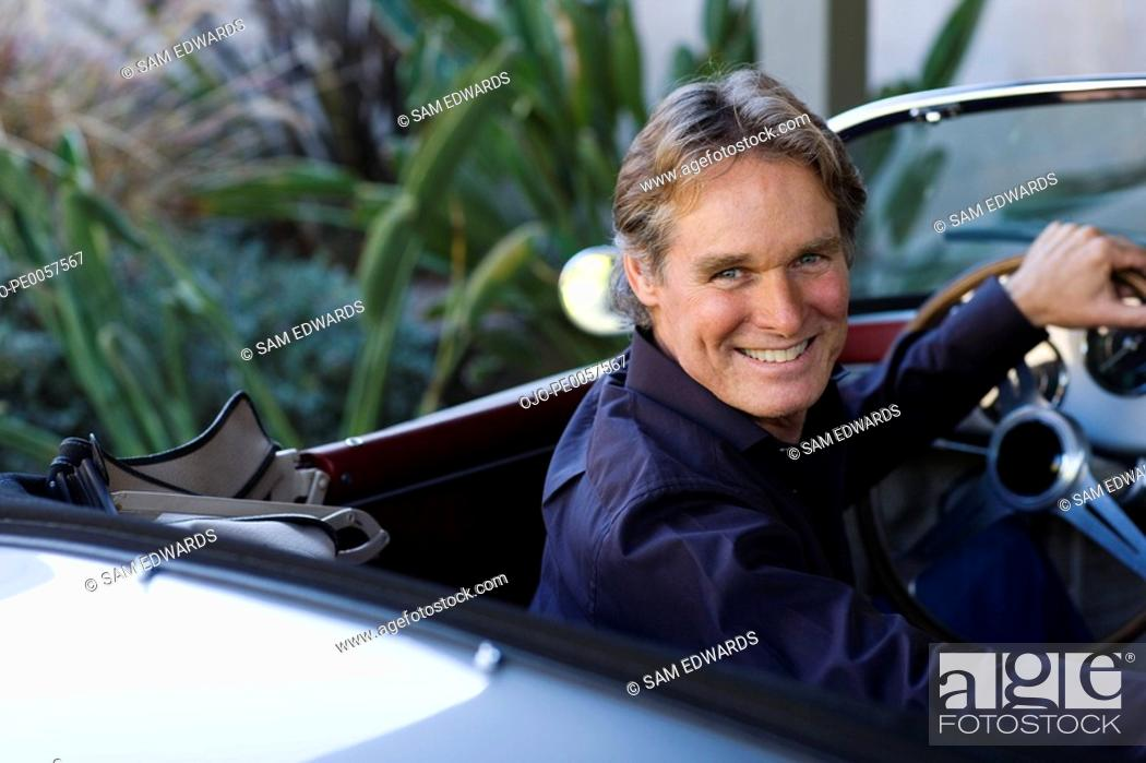 Stock Photo: Man sitting in convertible car smiling over his shoulder.