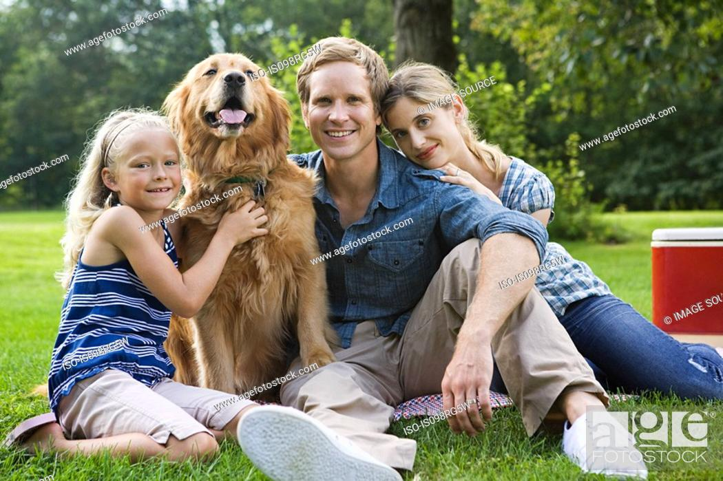 Stock Photo: Family in the park with golden retriever.