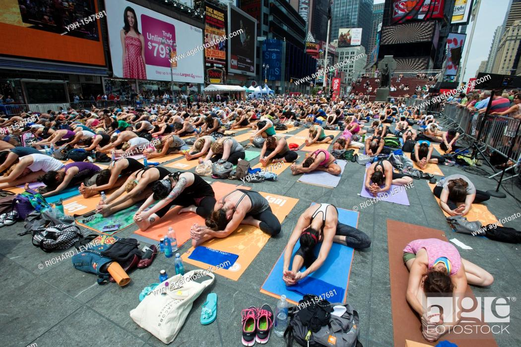 Stock Photo: Thousands of yoga practitioners in Times Square in New York participate in a group Bikram Yoga class observing the Summer Solstice The classes given throughout.