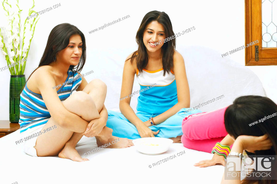 Stock Photo: Three young women talking on the bed.