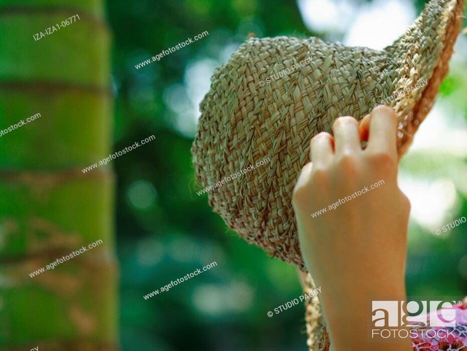 Imagen: Close-up of a woman's hands holding a straw hat.