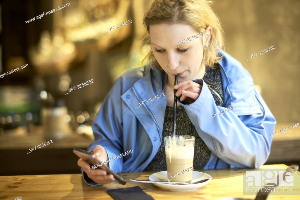 Imagen: Young woman using phone in cafe, Munich, Germany.
