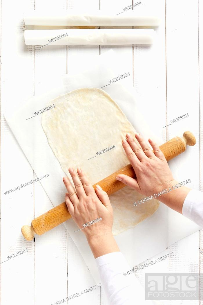 Stock Photo: Woman hands spreading a very thin strudel dough with a rolling pin on a sheet of kitchen paper with cornstarch to prevent sticking.