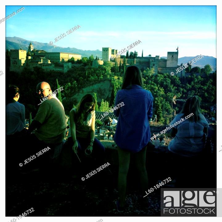 Stock Photo: Tourist enjoying the view of the Moorish Alhambra Palace from the Mirador San Nicolas in the El Albayzín or Albaicín quarter of Granada, Andalusia, Spain.