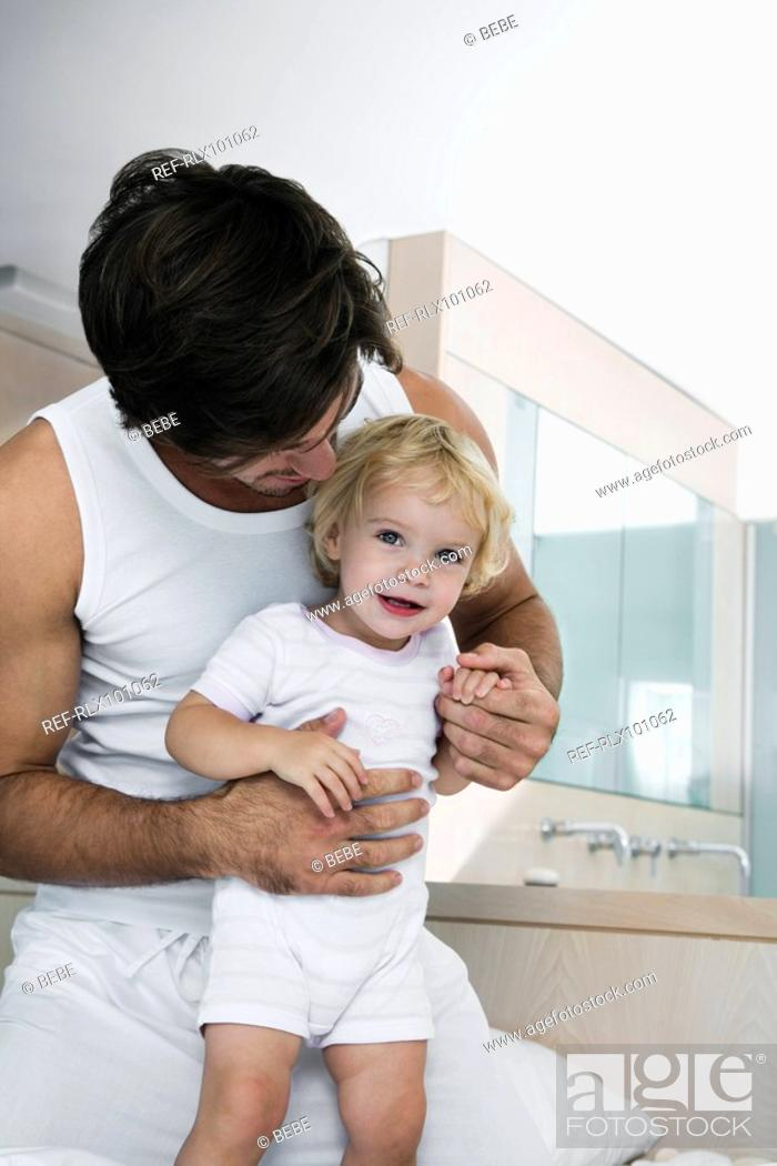 Stock Photo: Young father playing with baby 12-24 months in bed, holing baby, smiling.