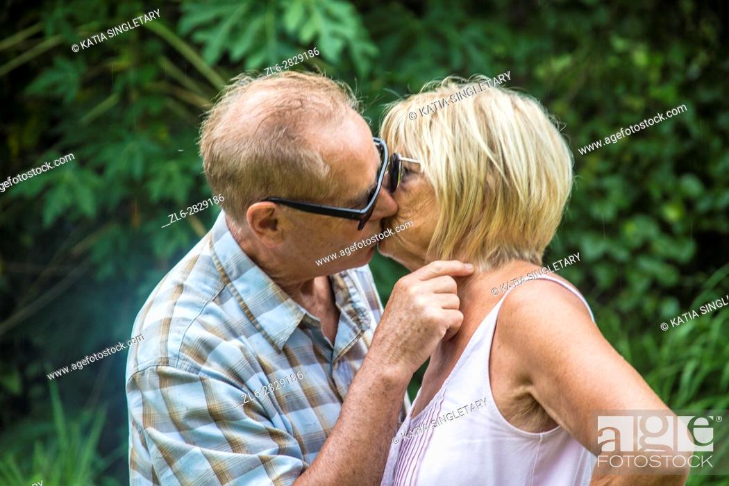 Stock Photo: Older mature retired caucaisna couple talking and kissing.