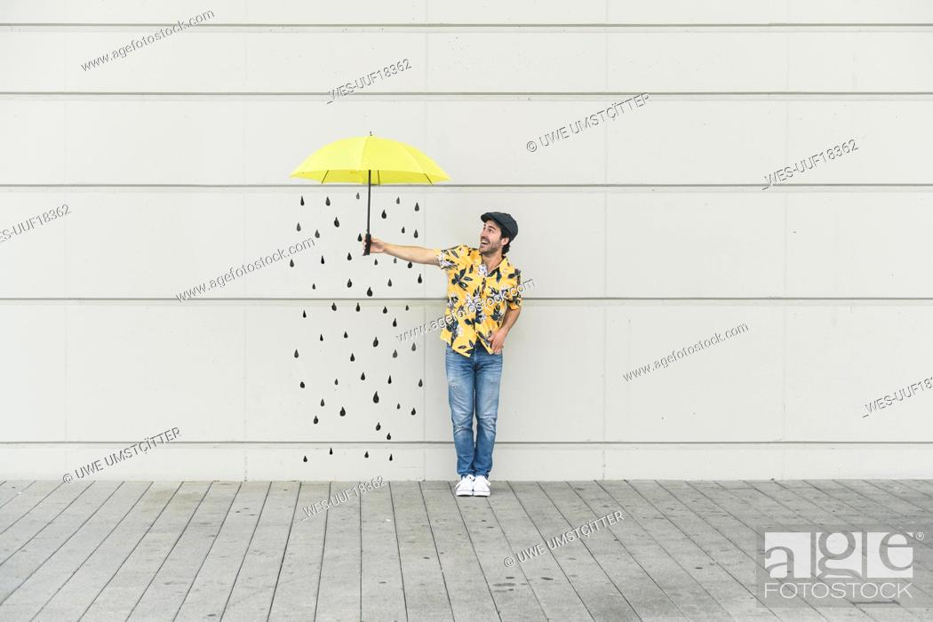Stock Photo: Digital composite of young man holding an umbrella at a wall with raindrops.