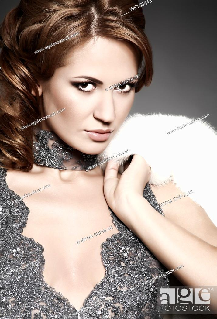 Stock Photo: Young woman in evening dress with fur.