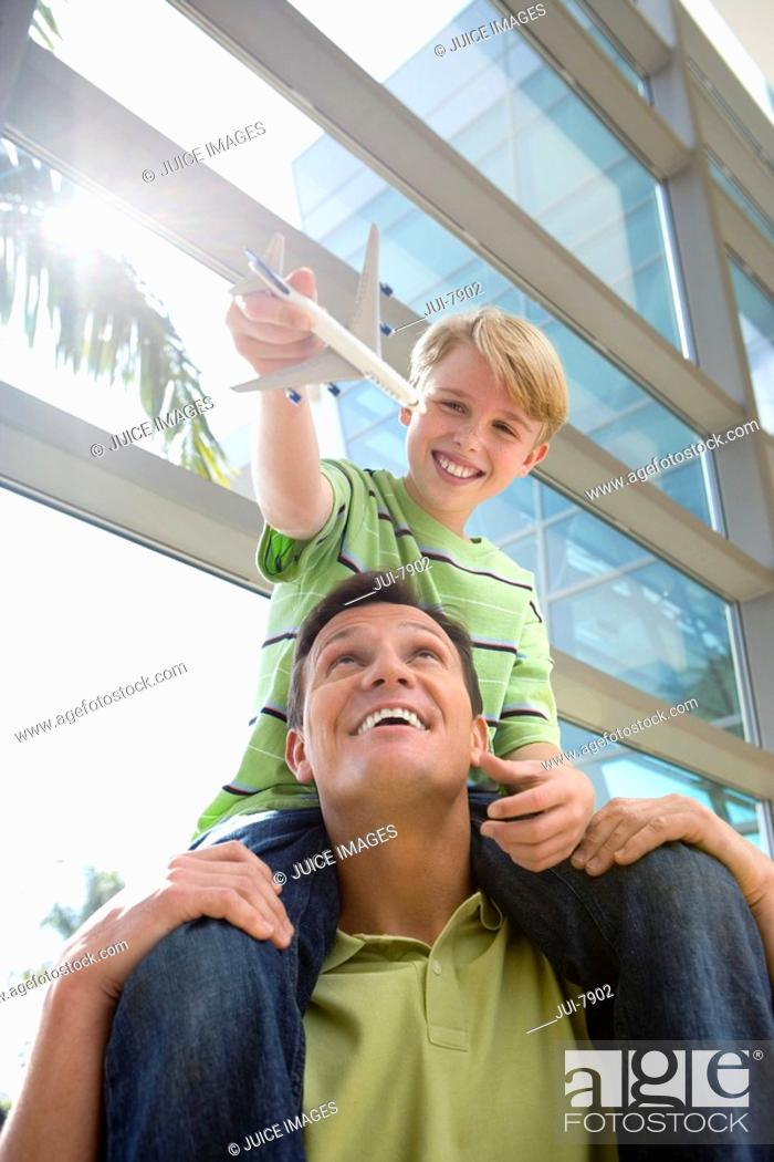 Stock Photo: Father carrying son 8-10 on shoulders in airport, boy holding toy aeroplane, smiling, front view, low angle view lens flare.