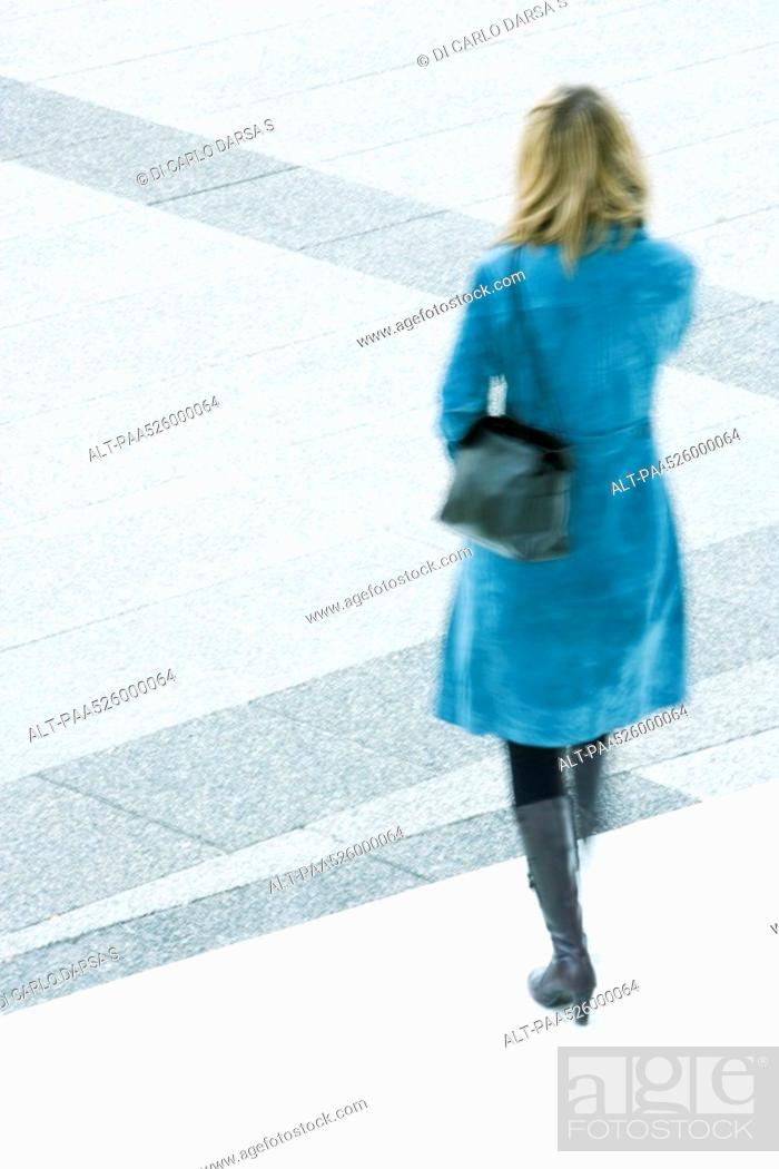 Stock Photo: Woman in blue overcoat descending steps outdoors.