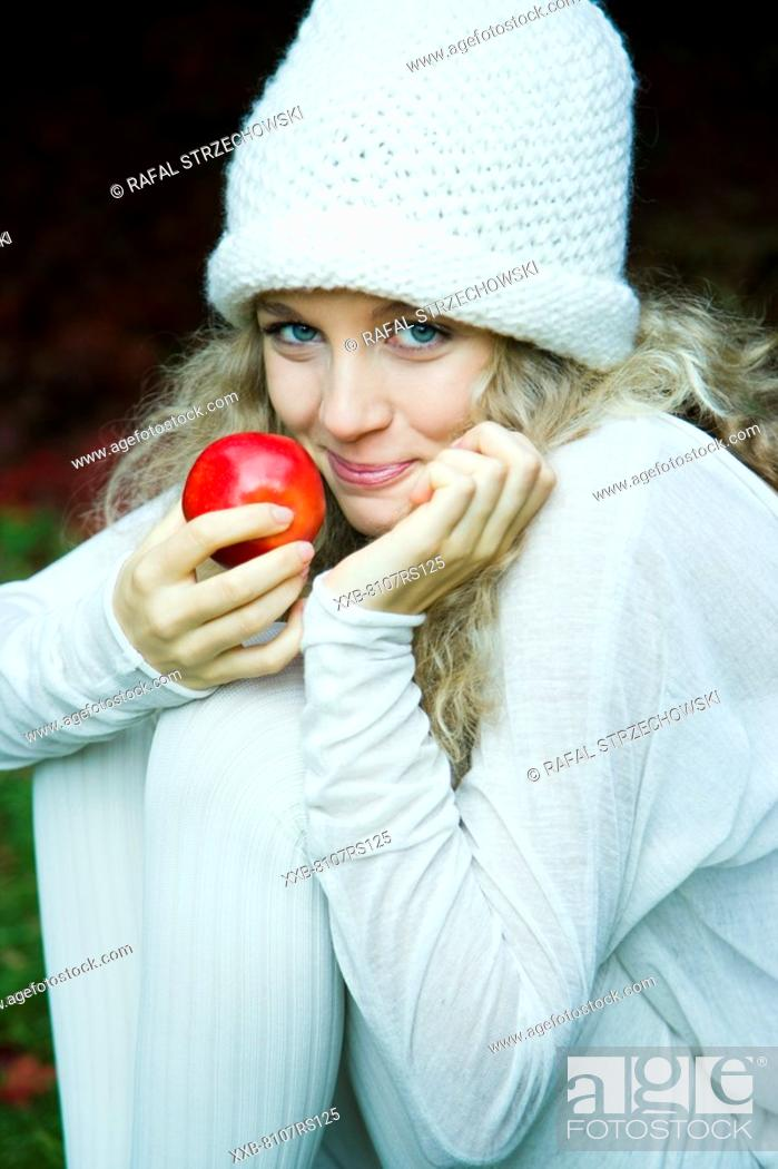 Stock Photo: Young woman eating apple in park.