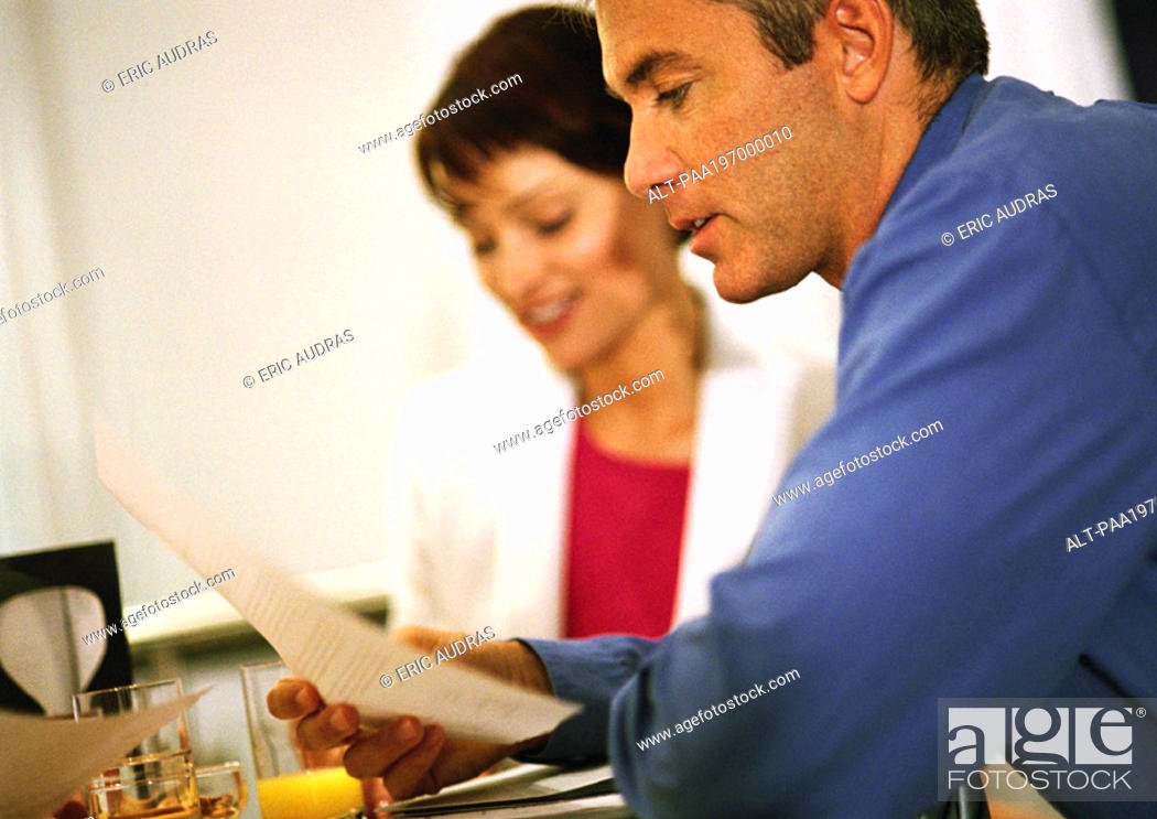 Stock Photo: Businesswoman sitting next to businessman reading document, side view, close-up.