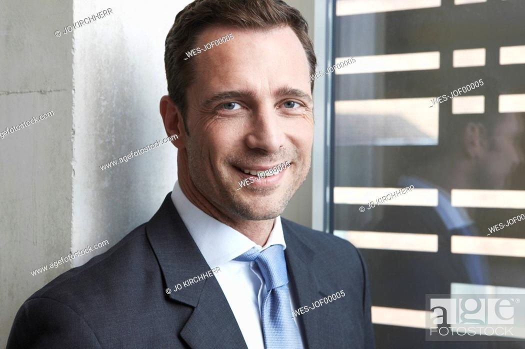 Stock Photo: Germany, Cologne, Businessman standing by window, smiling, portrait, close-up.