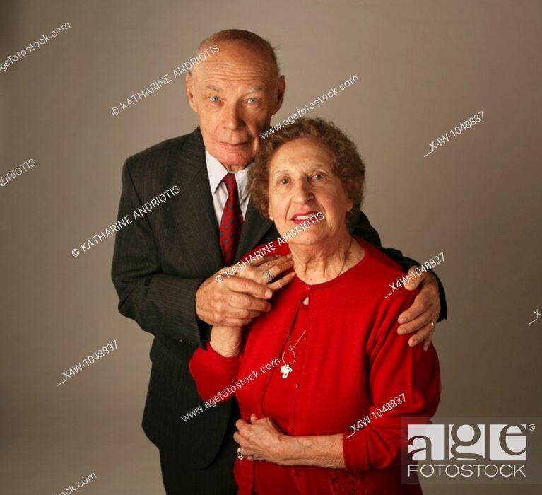 Stock Photo: Married senior couple posing for studio portrait.