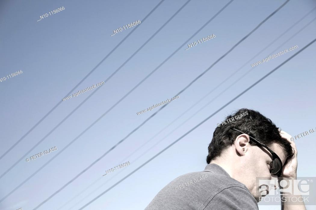 Stock Photo: Young man sitting beneath power lines.