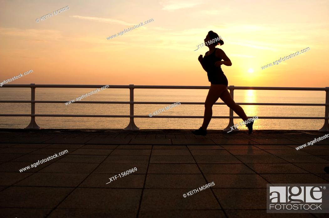Stock Photo: a woman jogger at dusk on a warm september evening aberystwyth promenade wales uk.