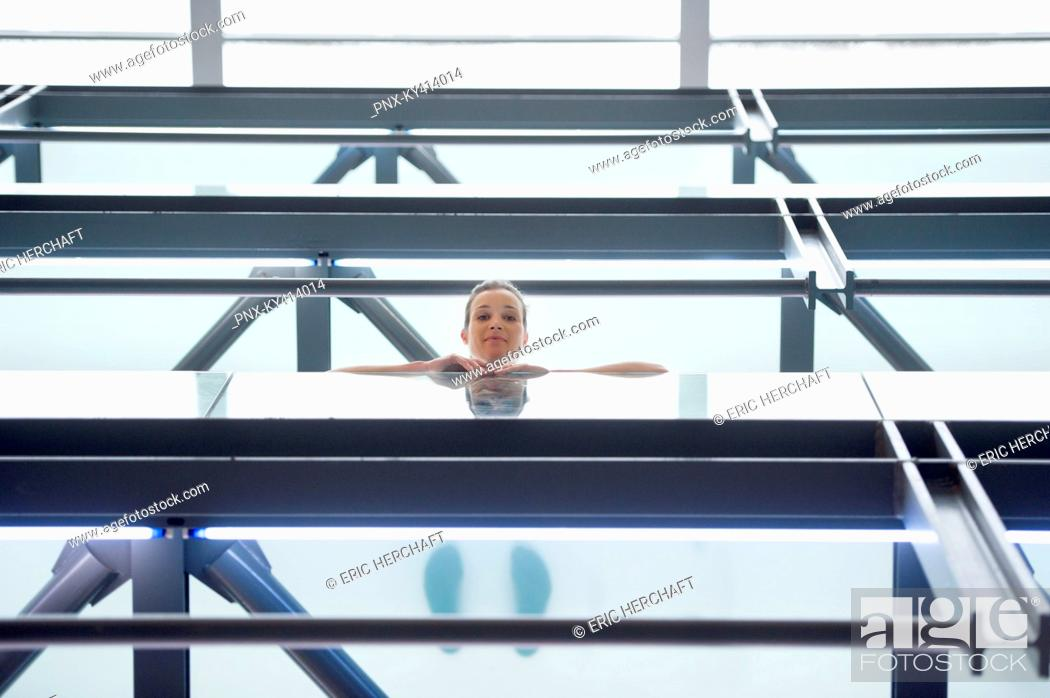 Stock Photo: Low angle view of a woman looking from the balcony of an office building.