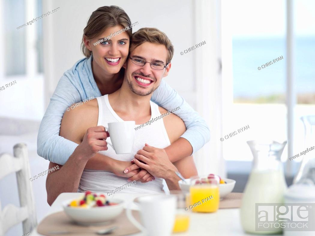 Stock Photo: Portrait of smiling couple enjoying breakfast at table.