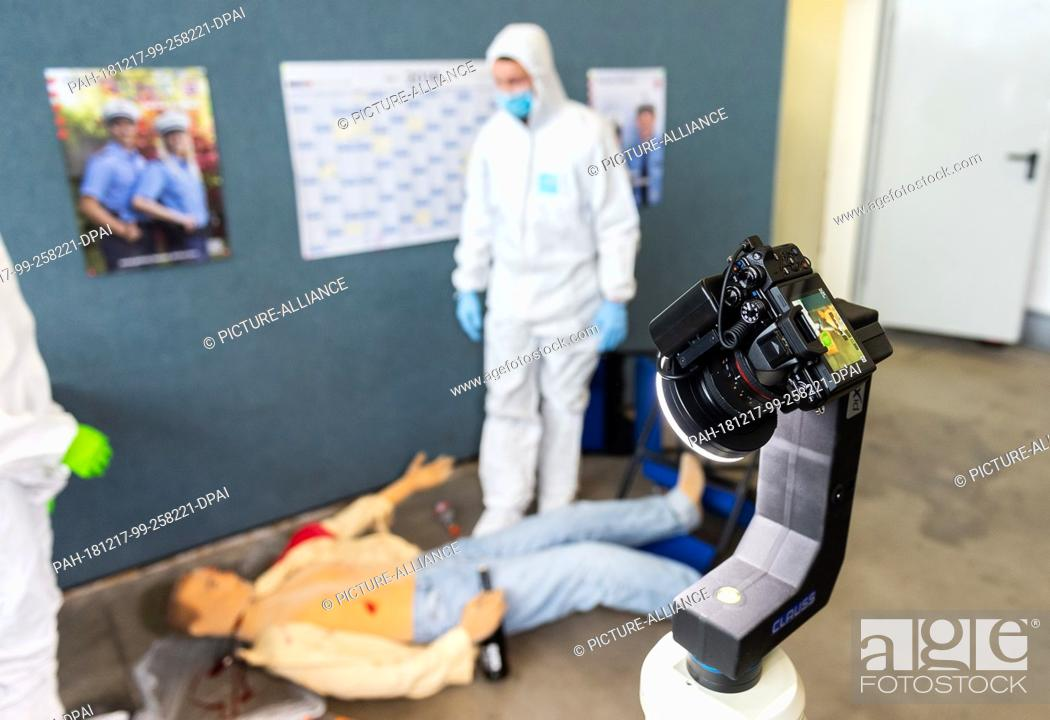 Stock Photo: 17 December 2018, Hessen, Gießen: A crime scene camera records a fictitious crime scene during a press conference at the police headquarters in Central Hessen.