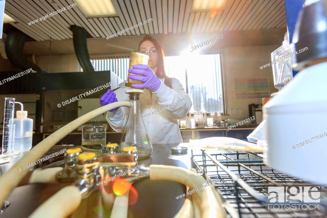 Stock Photo: Chemist assembling filter.