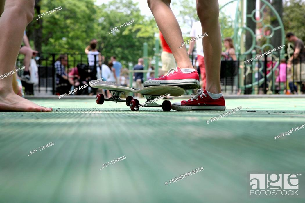 Stock Photo: Teenagers with skateboard in park.