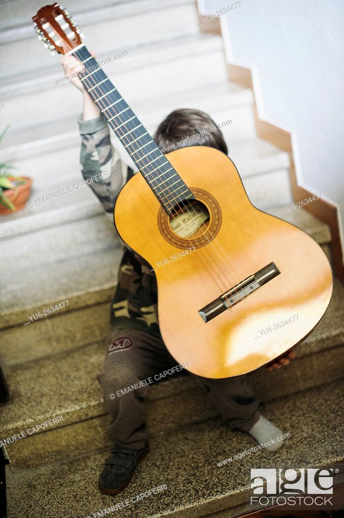Stock Photo: Portrait of little boy sitting on the stairs holding a guitar.