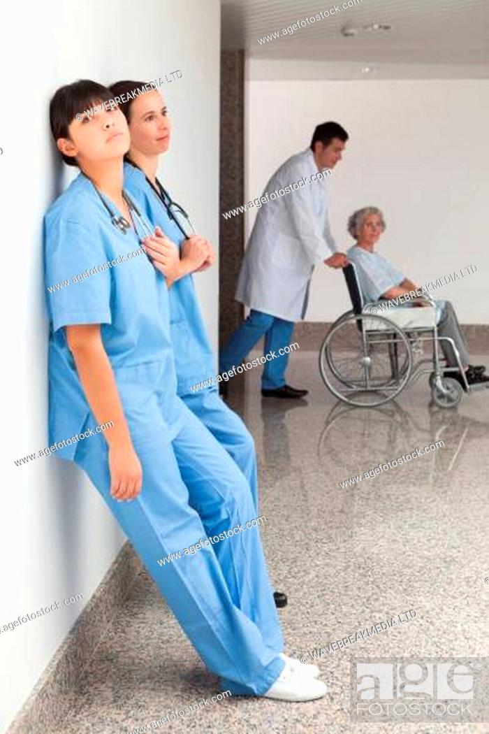 Stock Photo: Two nurses leaning on wall with doctor pushing patient in wheelchair.