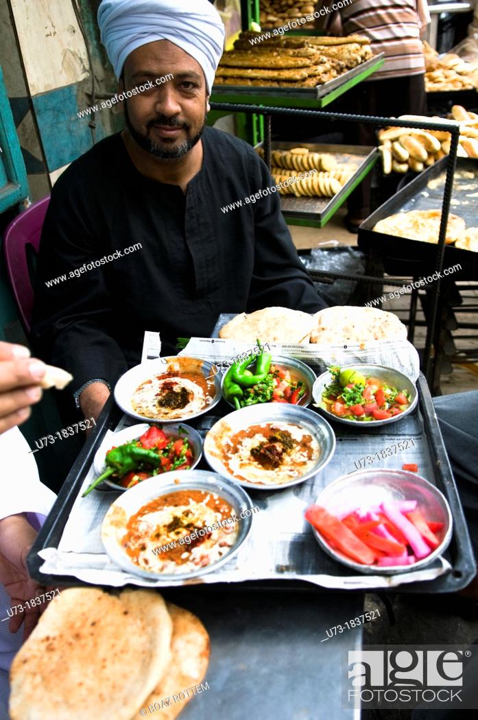 Stock Photo: An Egyptian man enjoys a traditional breakfast- Fuul Fava beans with bread and salad in a small street restaurant in Cairo.
