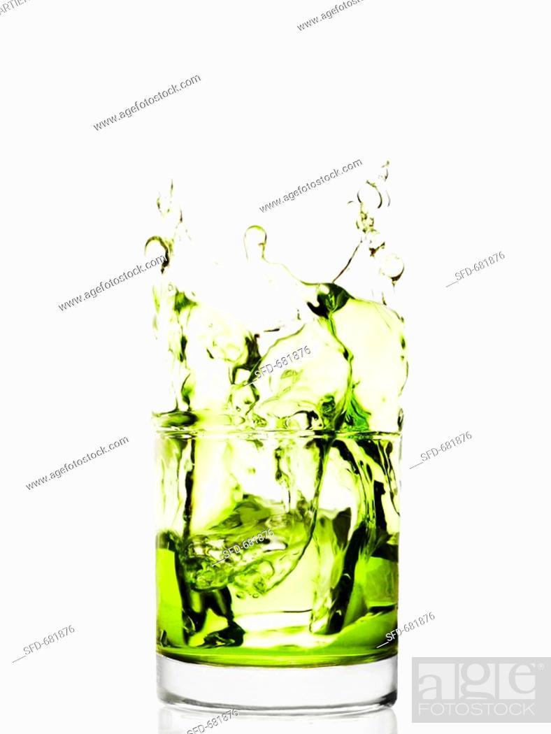 Stock Photo: Ice Splashing into a Glass of Green Liquid.