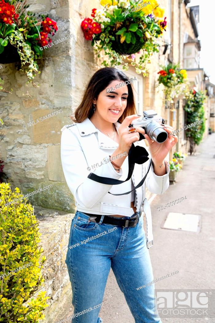 Stock Photo: Young woman on village street reviewing photos on digital camera, Cotswolds, England.