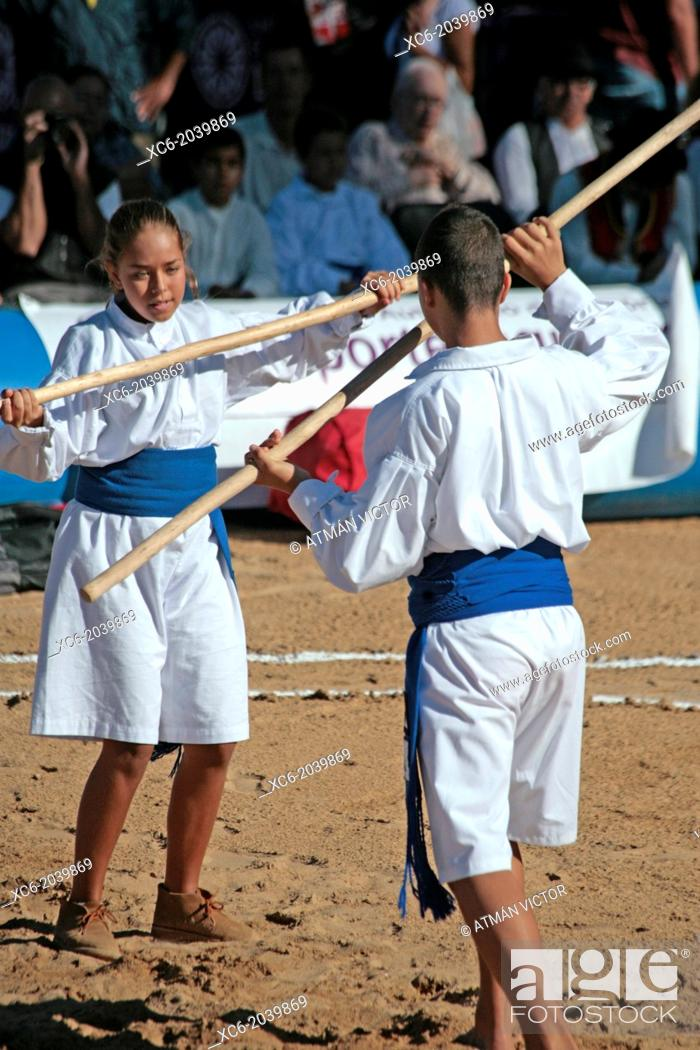 Stock Photo: Teens playing the canarian stick fighting in a public exhibition in the open air.