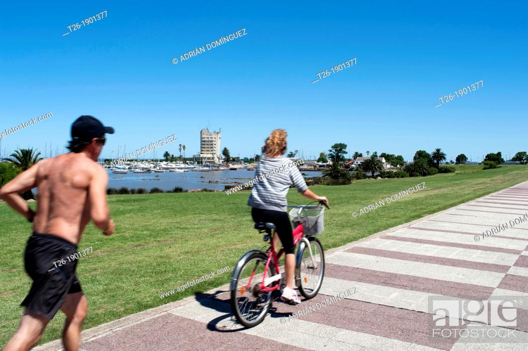 Stock Photo: A man runs back to a woman in a bike in the beach avenue of Montevideo city, Uruguay.