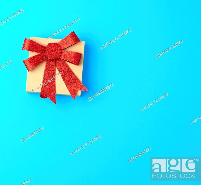 Stock Photo: closed brown gift box with a red shiny bow on a blue background, top view, copy space.