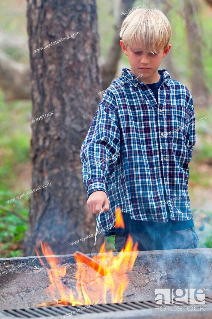 Stock Photo: Boy barbecuing sausage on flaming grill in forest, Sedona, Arizona, USA.