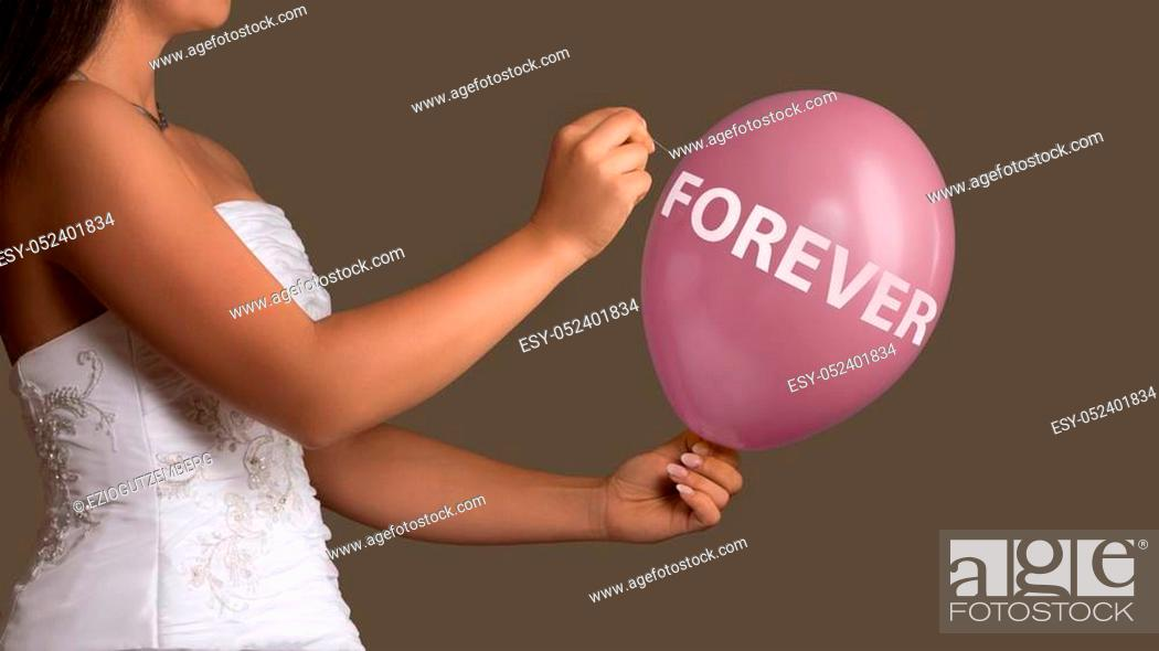 Stock Photo: Young bride in wedding dress lets a Balloon with Text burst with a needle.