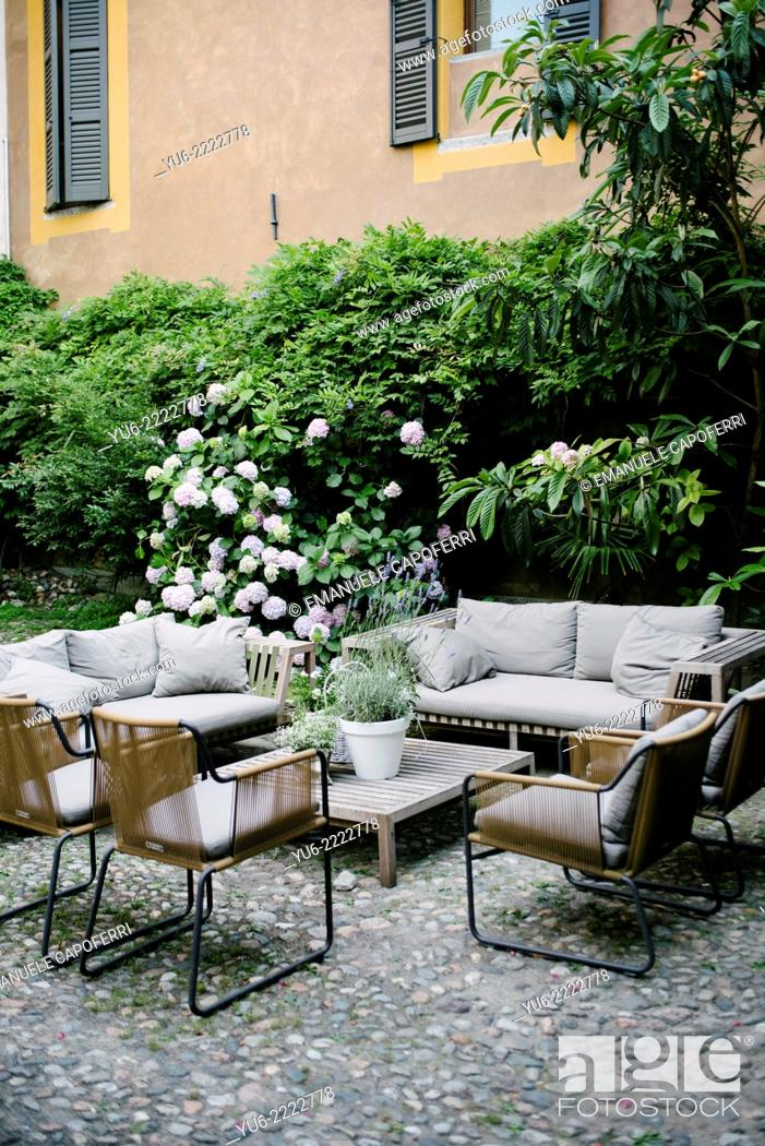 Stock Photo: Sitting area with plants and sofas and chairs with table.
